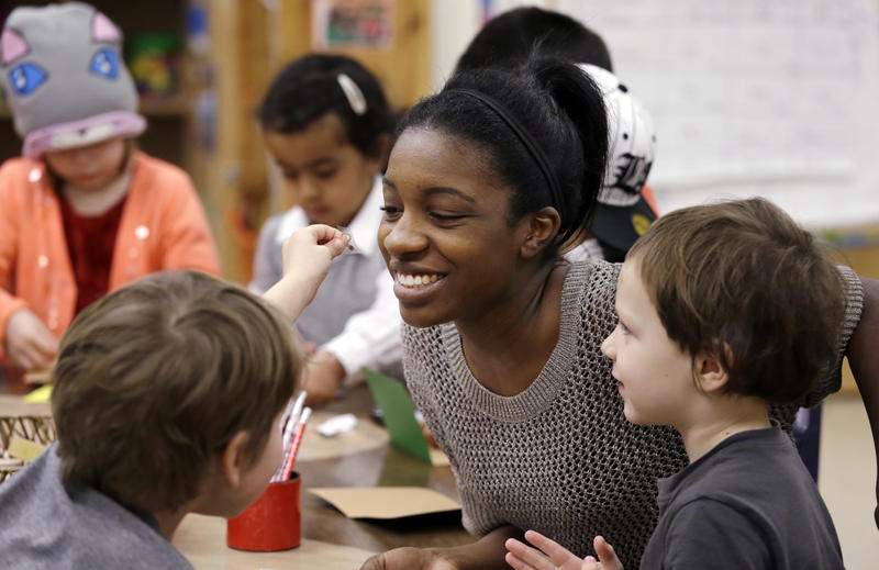 In this photo taken Friday, Feb. 12, 2016, assistant teacher D'onna Hartman smiles as she works with children at the Creative Kids Learning Center, a school that focuses on pre-kindergarten for 4- and 5-year-olds, in Seattle.