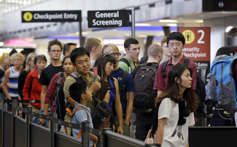 In this Tuesday, Aug. 11, 2015 photo, travelers wait in a security line at Seattle-Tacoma International Airport, in Seattle.