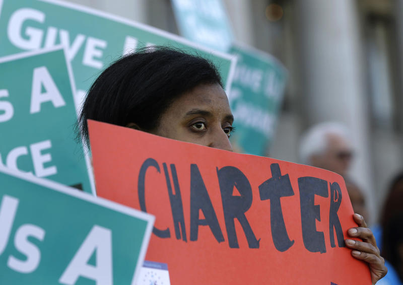 In this Feb. 25, 2016, file photo, Lavinda Trammell, of Tacoma, Wash., who said she is a parent of a child that attends a charter school, holds a sign during a rally in support of public charter schools at the Capitol in Olympia, Wash.