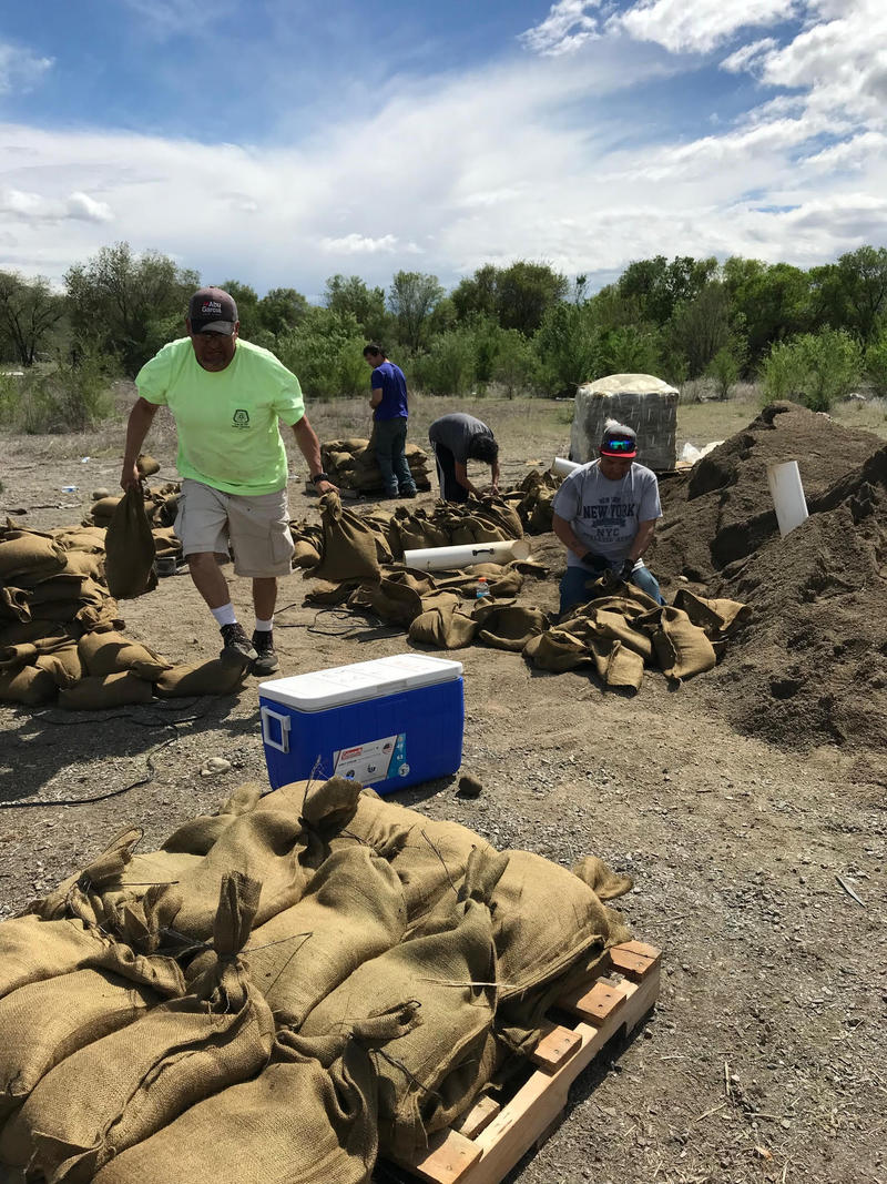 In this Thursday, May 10, 2018 photo provided by the Colville Tribes Environmental Trust Program, tribal members fill sandbags in Omak, Wash. The Okanogan River, which runs through Tonasket, reached a level of 19 feet (5.8 meters) early Friday morning.