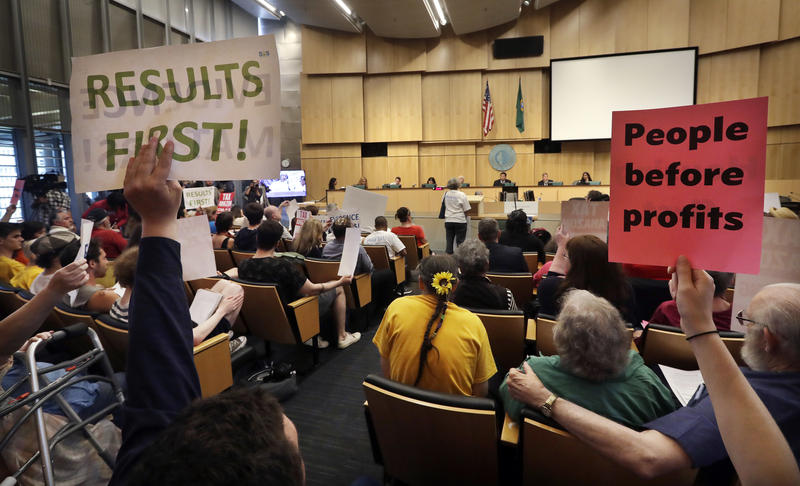 "Members of the public look on at a Seattle City Council meeting where the council was expected to vote on a ""head tax"" on May 14, 2018"