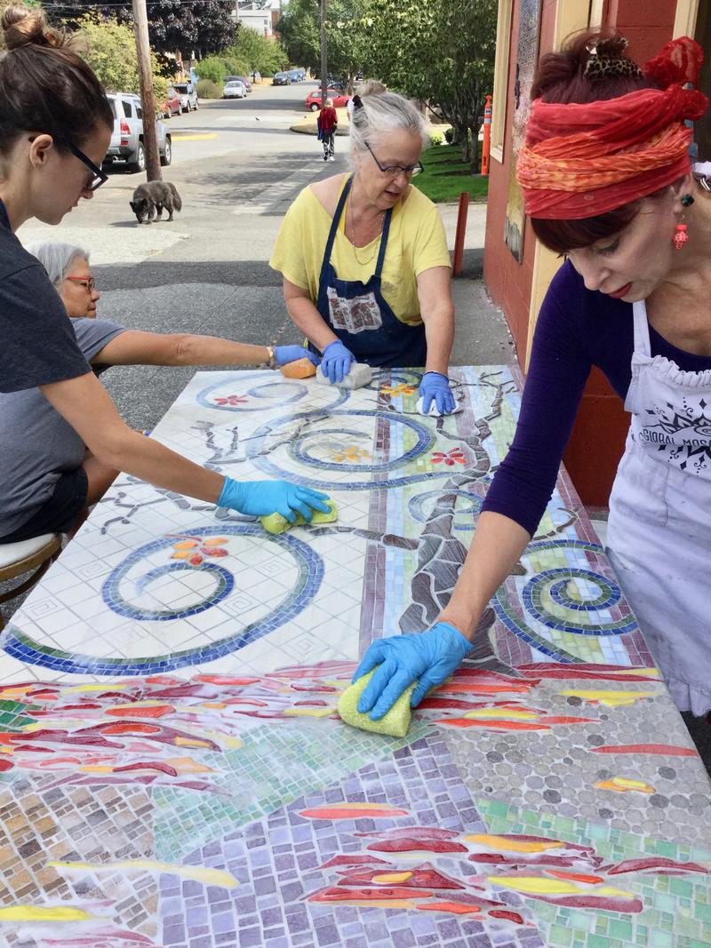 Outside Seattle Mosaic Arts in the Wallingford neighborhood, Emily Margherio, June Chang, Claire Barnett, and Janie Yakovlevitch work on a large mosaic just outside the studio.