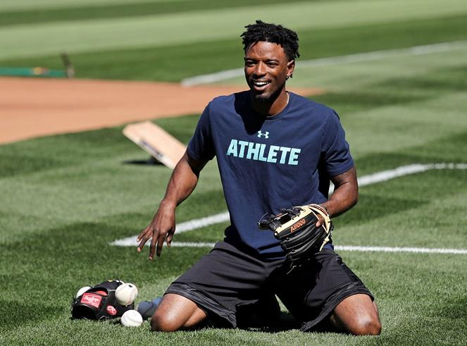 Mariners center fielder Dee Gordon smiles as he goes through a drill before the team's baseball game against the Texas Rangers Tuesday, May 15, 2018, in Seattle. He's expected to fill in at second base while Robinson Cano serves an 80-day suspension.