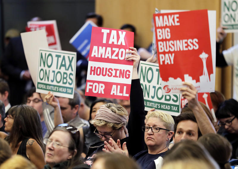 "People attending a Seattle City Council meeting hold up signs that say ""No Tax On Jobs"" and ""Tax Amazon, Housing For All"" Tuesday, June 12, 2018, as the council prepared to vote to repeal a controversial ""head tax"" on businesses."