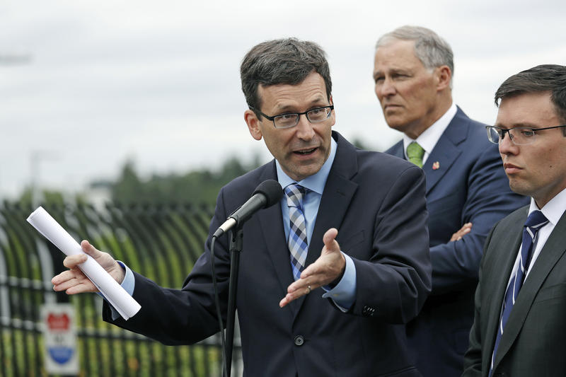 Attorney General Bob Ferguson, left, speaks at a press conference announcing a lawsuit against the Trump administration over a policy of separating immigrant families illegally entering the United States.
