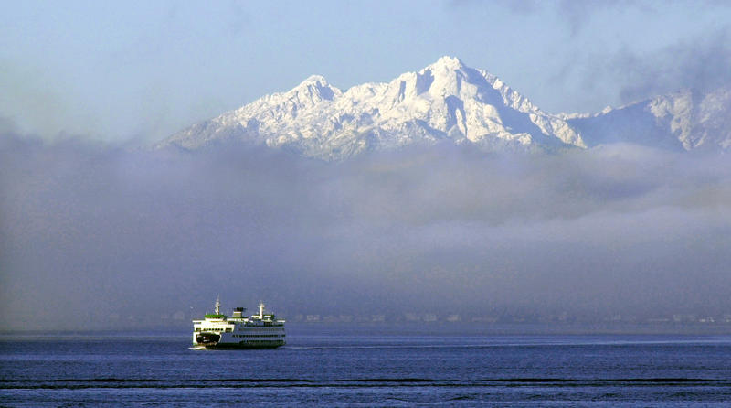 In this Dec. 8, 2003, file photo, a Washington state ferry emerges from a fog bank on Puget Sound near Bainbridge Island as the Olympic Mountains are seen between cloud banks as seen from Seattle.