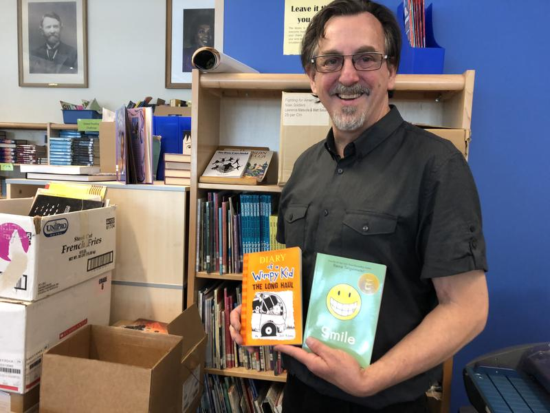 Jeff Treistman, librarian at Denny International Middle School in West Seattle, shows some of the books sixth graders will be able to take home for free.