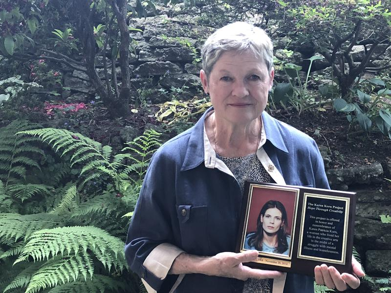 Pat Swain holds a plaque in honor of her daughter, Karen Korn. The plaque states the mission of the Karen Korn Project, which is to provide hope through creativity.