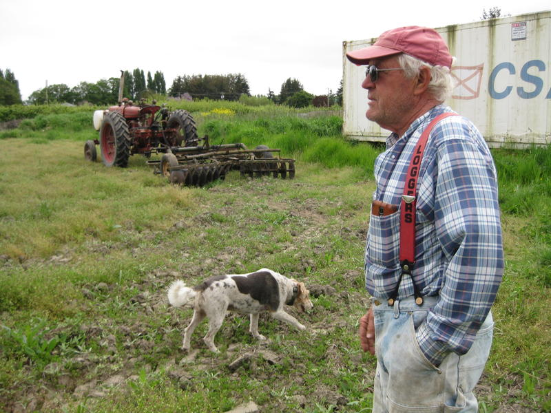 Nash Huber near his greenhouses with his dog, Prancer. Huber says he plans to use this field as a perk for employees, with plots where they can grow their own produce for personal use.
