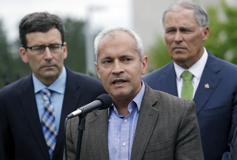 Northwest Immigrant Rights Project director Jorge Baron, center, speaks as Attorney General Bob Ferguson, left, and Washington Gov. Jay Inslee, look on at a news conference on June 21, 2018