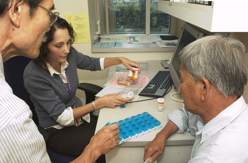 Tiffany Erikson, a pharmasist with Harborview's International Medicine Clinic, consulting with a patient and a translator.