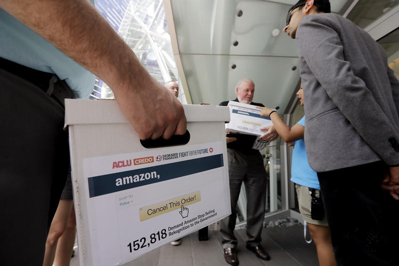 Faith leader Rev. Paul Benz, center, and Shankar Narayan, ACLU, wait with volunteers delivering petitions to Amazon.