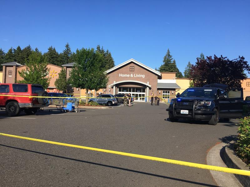 Police tape blocks off part of a parking lot at the Walmart in Tumwater, after a shooting and attempted carjacking. Police say the shooter was killed by an armed bystander.