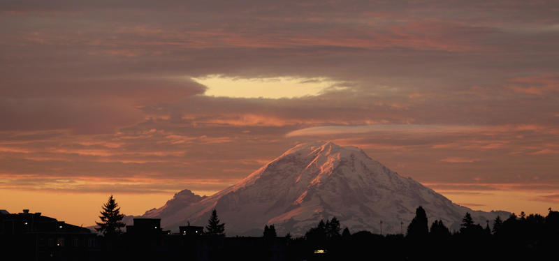Mount Rainier is illuminated at dawn beneath a brilliant cover of clouds as seen from Seattle, about 50 miles away, Wednesday, Sept. 21, 2011.