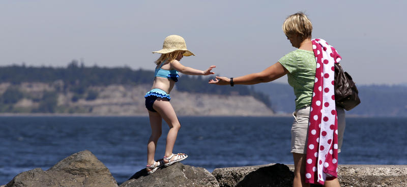 Macey Pirak, 5, reaches for the hand of her friend Carrie Gray as they scramble over rocks on Tuesday, July 1, 2014, at a beach on the Puget Sound in Mukilteo, Wash. Temperatures are expected to hit near 90 in nearby Seattle.