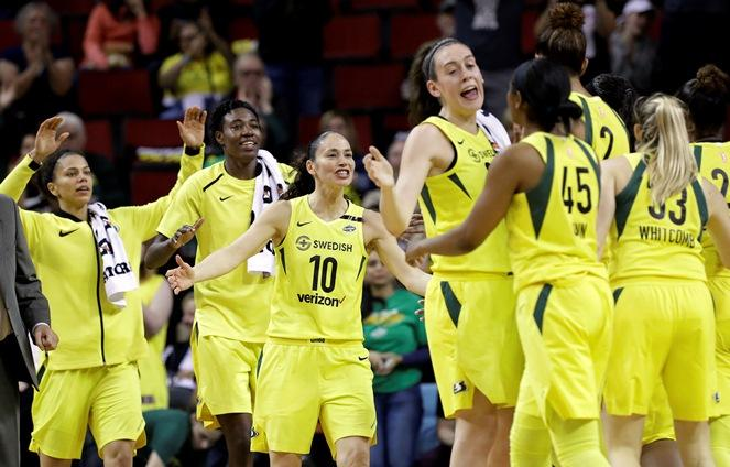 Seattle Storm's Alysha Clark, left, Natasha Howard, Sue Bird (10) and Breanna Stewart come off the bench to greet teammates during a timeout in the first half of a WNBA basketball game against the Connecticut Sun on Friday, June 15, 2018, in Seattle.