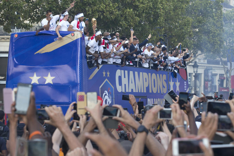 Well-wishers cheer the victorious French team parading aboard a bus on the famed Champs Elysees avenue in Paris. France won the FIFA World Cup on Sunday with a 4-2 victory over Croatia.
