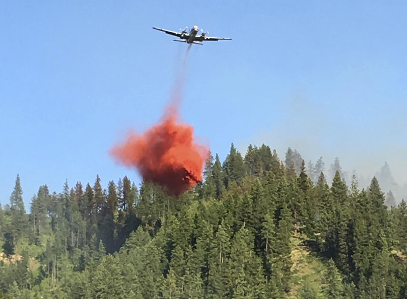An air tanker drops fire retardant on forest land as a wildfire burns.