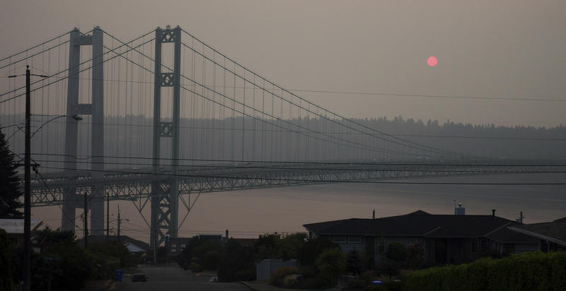 The sun is seen through smoky air as it sets, Sunday, Aug. 19, 2018, behind the Narrows Bridge in Tacoma, Wash. Poor air quality was common across parts of the Pacific Northwest all week as winds pushed smoke from surrounding wildfires into the region.