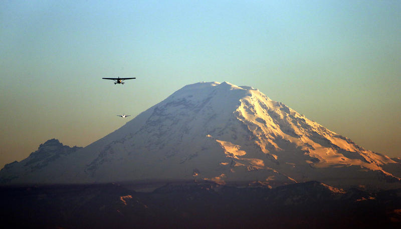 A pair of small airplanes flies into Boeing Field and in view of Mount Rainier at dusk Wednesday, Jan. 16, 2013, in Seattle.