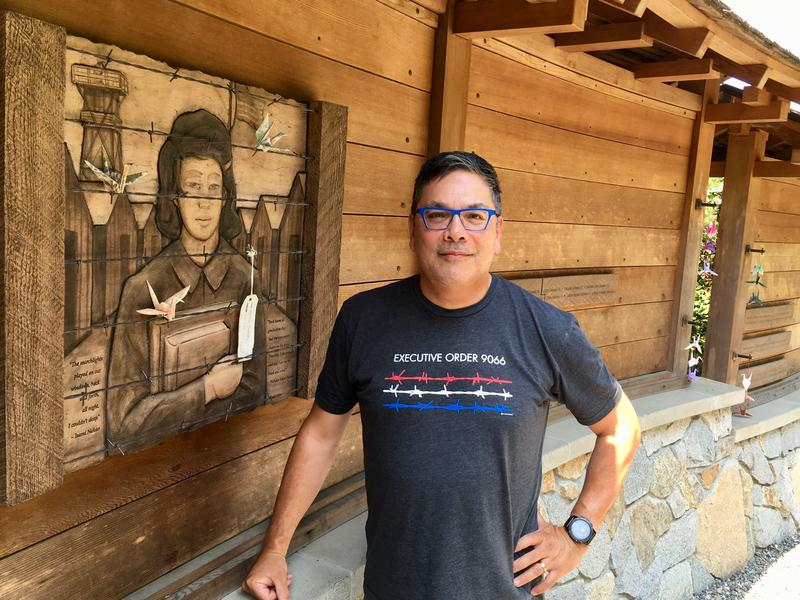Glenn Nelson beside one of the story panels at the Bainbridge Island Japanese American Exclusion Memorial.
