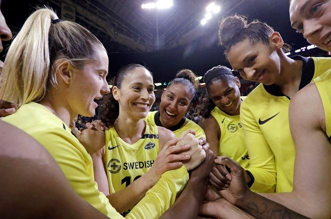 Seattle Storm's Sami Whitcomb, Sue Bird, Kaleena Mosqueda-Lewis, Courtney Paris and Mercedes Russell, from left, huddle with teammates after the Storm defeated the Connecticut Sun 103-92 in a WNBA basketball game Friday, June 15, 2018, in Seattle.