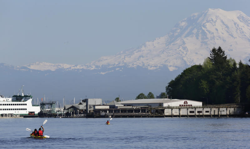 With Mount Rainier in the background, kayakers paddle near Owen Beach in Point Defiance Park, Monday, April 18, 2016, in Tacoma, Wash.