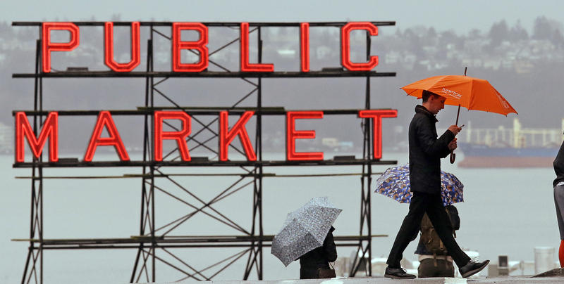In this Jan. 18, 2017, file photo, pedestrians huddle under umbrellas as they walk past the Pike Place Market and in view of Elliot Bay, behind, in Seattle.