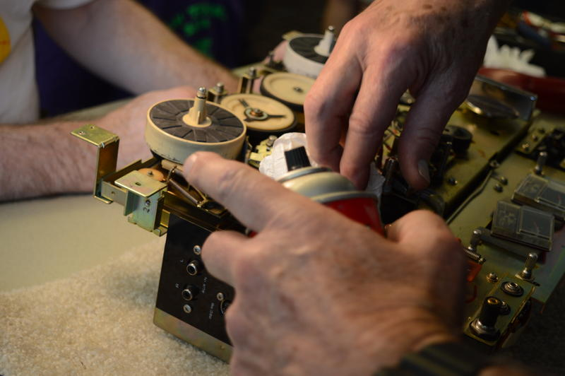 "A ""fixer"" working on an old reel to reel tape player at a repair event at the Skyway Library near Renton, WA. Dozens of these events take place throughout Western Washington every year. All repairs are made free of charge."