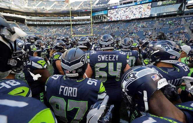 Seahawks players, including offensive guard J.R. Sweezy (64) huddle during warmups before a preseason game against the Oakland Raiders, Thursday, Aug. 30, 2018, in Seattle.