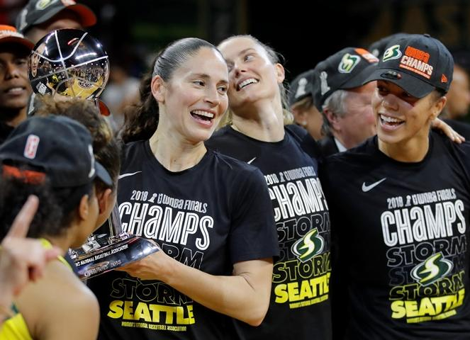 Seattle Storm guard Sue Bird, left, holds the championship trophy with her teammates during after winning Game 3 of the WNBA basketball finals, Wednesday, Sept. 18 2018, in Fairfax, Va. Seattle Storm won 98-82.