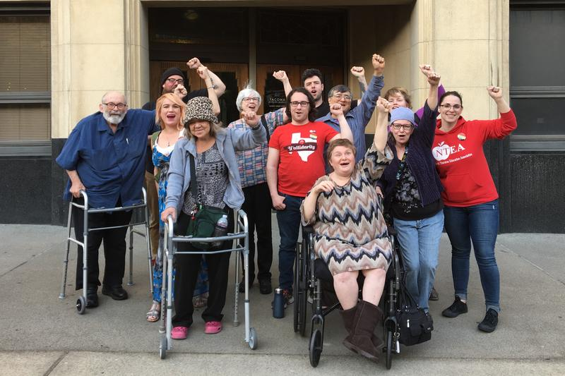 Tenants of the Tiki Apartments and their supporters outside Tacoma City Hall in April.