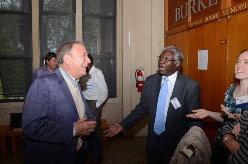Calestous Juma, center, jokes with one of his leading critics, Phil Bereano, at left