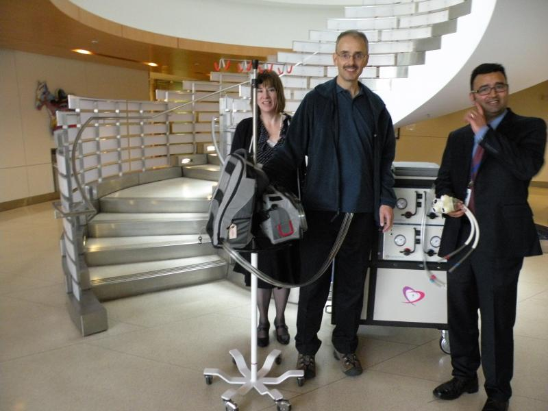 Chris Marshall shows off the mobile pump and battery pack for his artificial heart, with his wife Kathy and surgeon Dr. Nahush Mokadam at his side (Mokadam is also holding a sample of an artificial heart), at UW Medical Center.