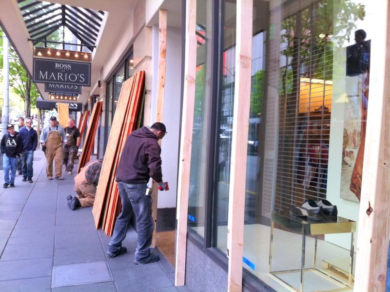 Business owners begin boarding up downtown Seattle after an afternoon of violent May Day protests.
