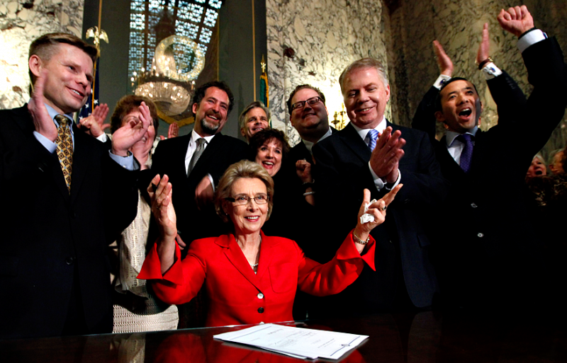 Governor Christine Gregoire raises her arms as legislators and supporters cheer behind her after she signed into law a measure that legalizes same-sex marriage Feb. 13, 2012, in Olympia.