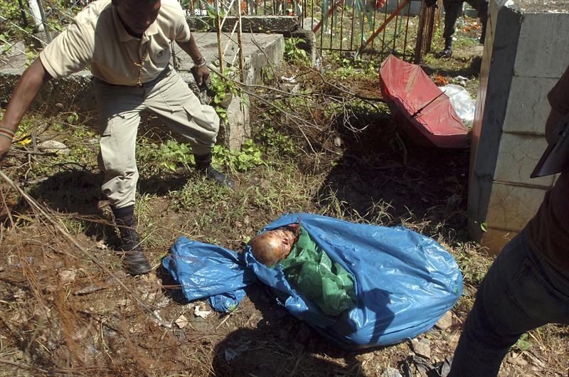 National police officers inspect a bag containing a mutilated body that was found inside the cemetery in Tegucigalpa, Honduras, 2010. Honduras has become one of the deadliest cities in Central America..
