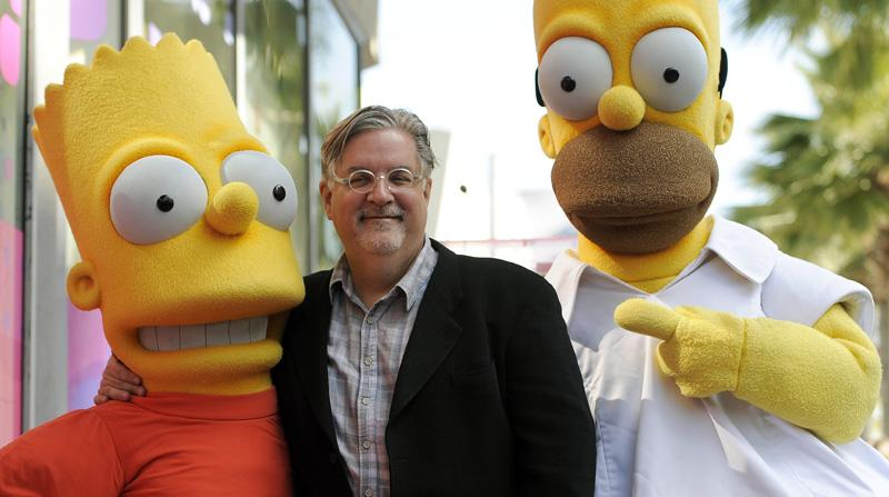 "Matt Groening, creator of the animated series ""The Simpsons,"" poses with his character creations Bart Simpson, left, and Homer Simpson earlier this year."