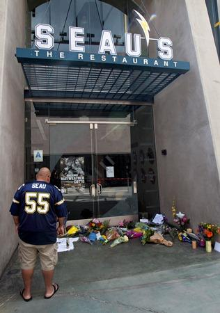 A man wears a Junior Seau replica uniform in front of Seau's restaurant in San Diego. Former San Diego Chargers star Seau was found shot to death at his home Wednesday in what police said appeared to be a suicide.