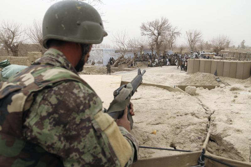 An Afghan soldier is seen in a guard tower at a military base as civilians gather outside in Panjwai, Kandahar province south of Kabul, Afghanistan, on Sunday.
