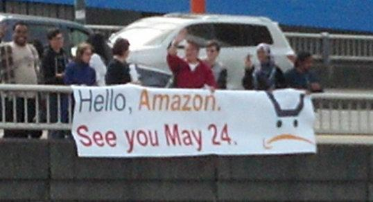 In this photo from Working Washington website, protesters give Amazon a taste of what the group hopes will be a big day for them, and the company.