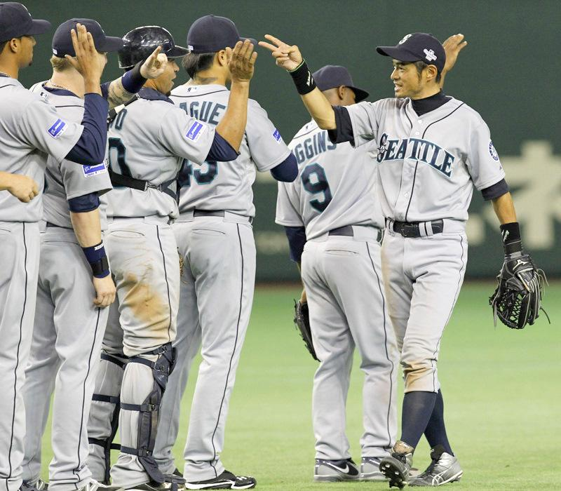 Seattle Mariners rightfielder Ichiro Suzuki, right, celebrates with teammates after beating the Oakland Athletics 3-1 in their American League season opening MLB baseball game at Tokyo Dome in Tokyo on Wednesday.