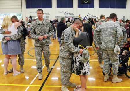 Spec. Tomas Marks, center, kisses an unidentified woman during a welcome home ceremony after about 150 soldiers from the Army's 4th Stryker  brigade returned to Joint Base Lewis-McChord, Wash. on Thursday, Aug. 19, 2010. They are part of the last ...