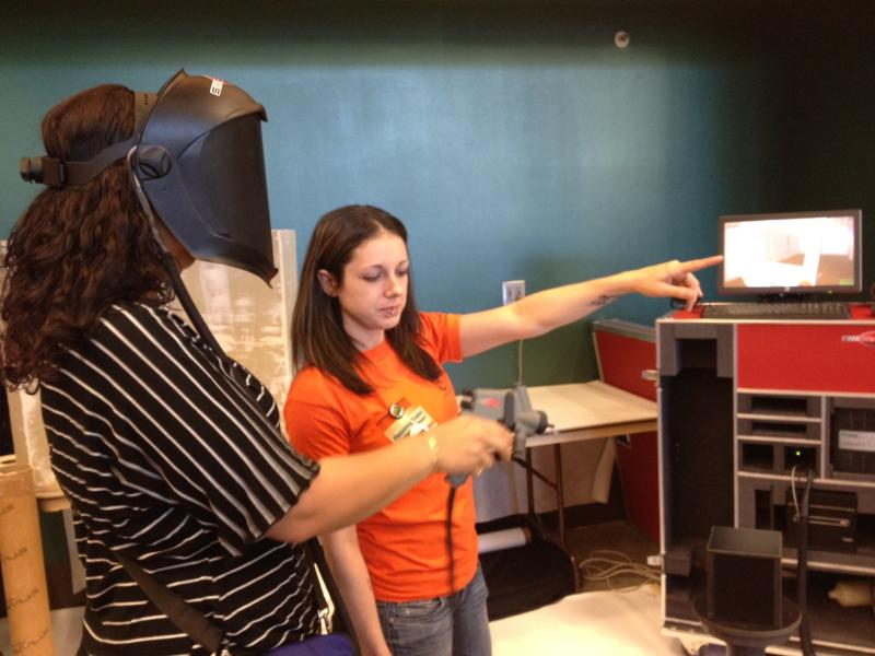 """Colette Hayes guides Jerelyn Hampton on a 3D simulator that teaches apprentices how to spray paint. Hayes says she's seen friends go to college and incur huge debts, then get no work. """"I worked every day and made money,"""" she says of her apprenticeship."""