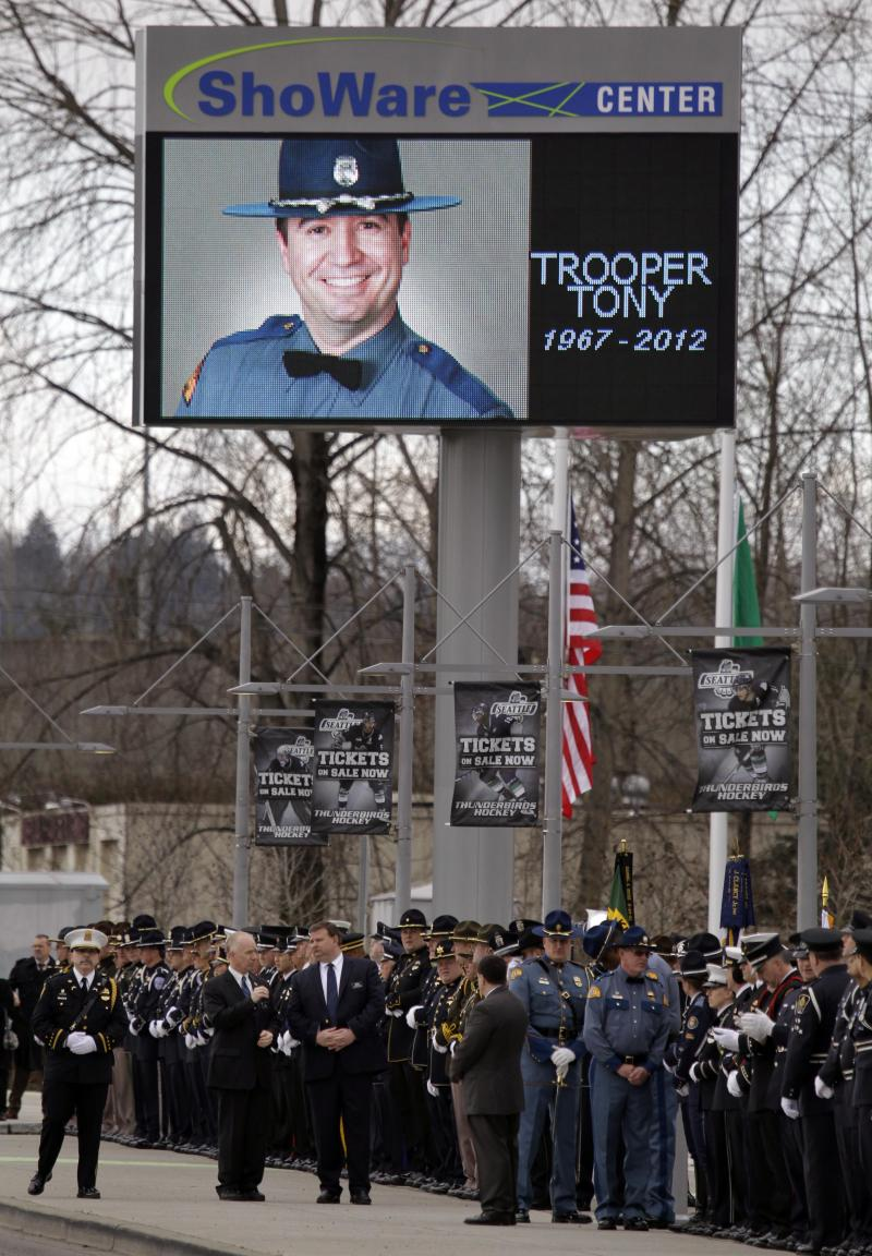 Police honor guard officers wait for the arrival of a motorcade procession before a memorial service for Washington State Trooper Tony Radulescu today in Kent, Wash. Radulescu was shot and killed Feb. 23 during a traffic stop in Gorst,