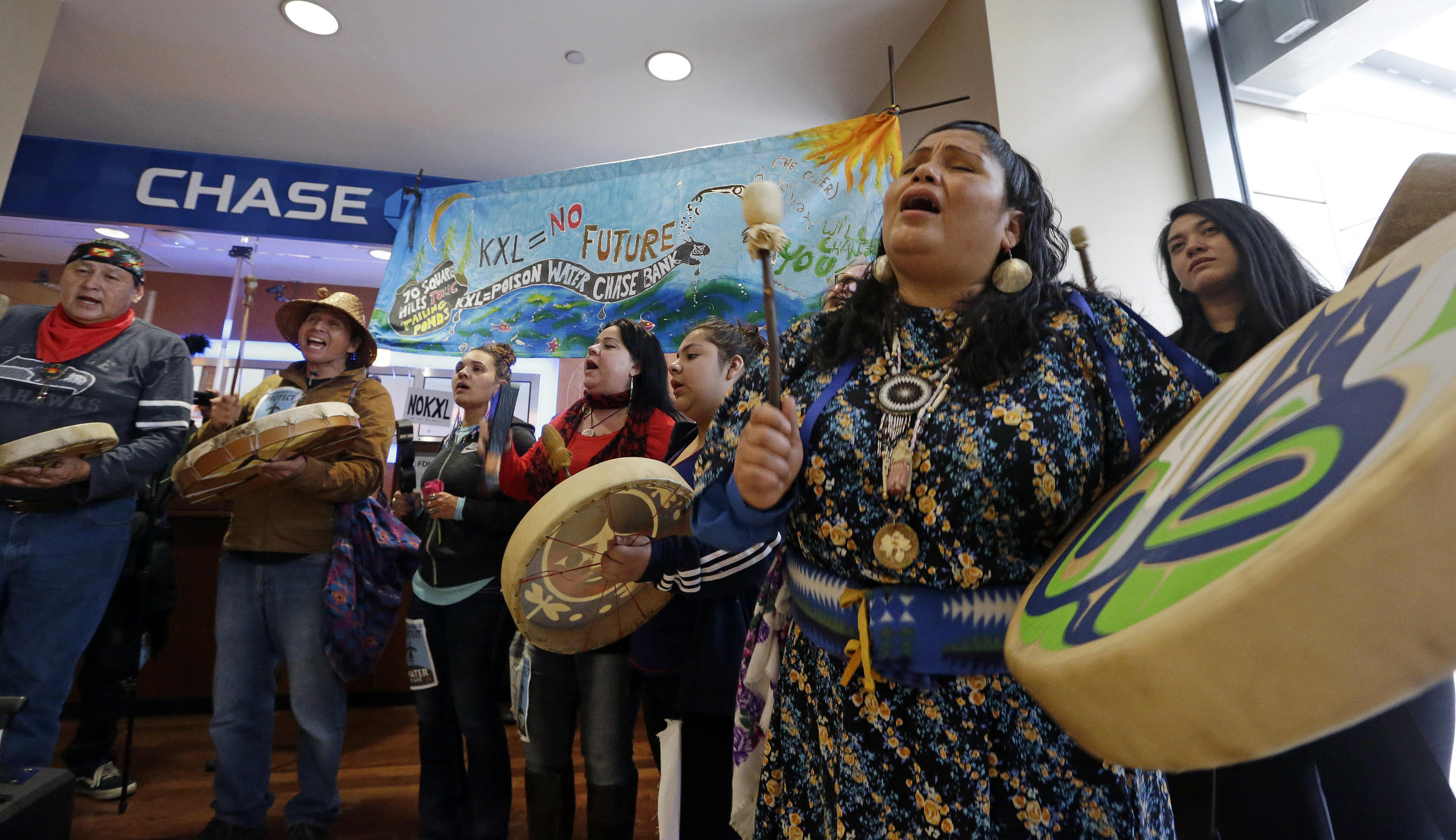 Roxanne White, right, a member of the Yakama Nation, sings during a protest  inside a Chase bank branch Monday, May 8, 2017, in Seattle.