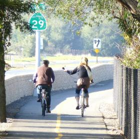 "Philip Sales, chief trail planner for the Napa Valley Vine Trail, and KRCB reporter Danielle Venton chat while biking along the trail's ""flagship"" mile."