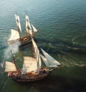 The Lady Washington and the Hawaiian Chieftain jockey for position in a simulated battle exercise. Paying customers can watch and even participate in the events on board, while spectators along the shore can watch observe from a safe distance.