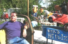 Josef Szuecs sits in the garden area outside his Renga Arts gallery, surrounded by colorful junk art sculptures created by Patrick Amiot. which are sold there.