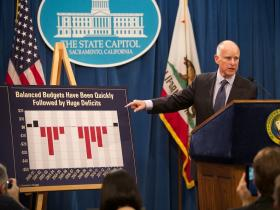 Calif. Gov. Jerry Brown points to a chart of recent state budget deficits and surpluses as he unveils his 2014-15 budget proposal in January.